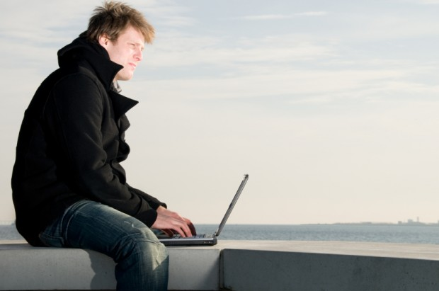 Man wears coat and wortks with laptop at the sea