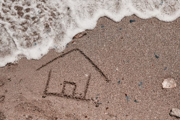 high angle view of house draw on the beach and wave coming over it.