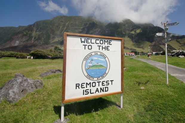 "A road sign reading ""Welcome to the remotest island,"" mountains are visible in the background."