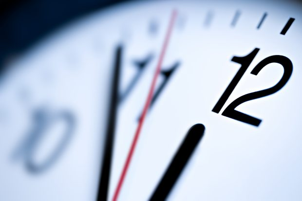 Picture of an analog clock approaching 12pm.