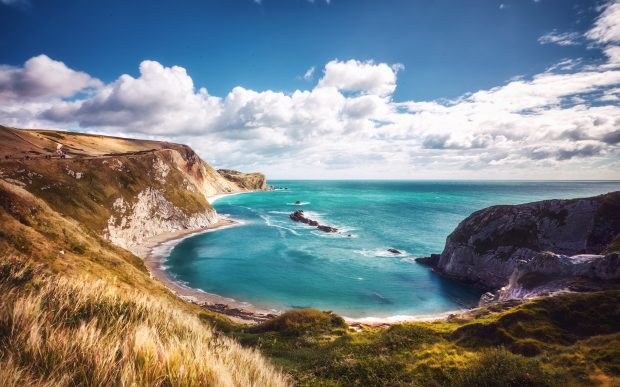 Image of Durdle Door in Dorset. Turquoise waters in a bay under blue sky and white cloud.