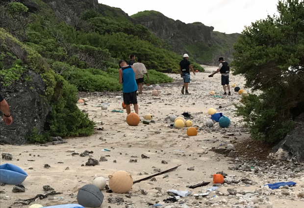 This image shows the terrible damage that global marine pollution is having on a UK Overseas Territory. Image of five individuals amongst litter on a beach