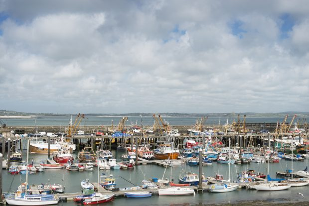 Newlyn Harbour filled with boats and fishing vessels with views across Mounts Bay with St. Michaels Mount visible in the distance. A few people visible in the harbour area.