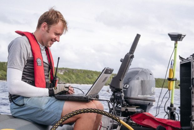 Man working on laptop on a boat