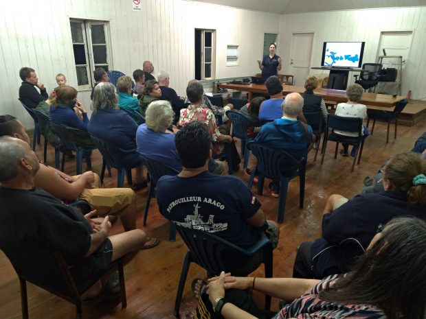 Residents of Pitcairn Island listening to a presentation in a town hall.